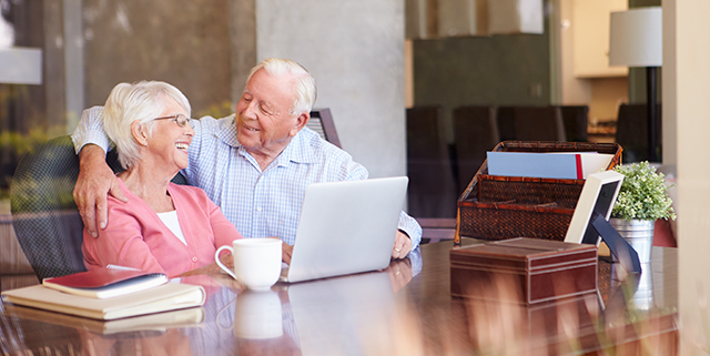 Happy elderly couple sitting together and working on a laptop