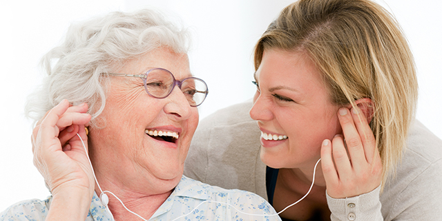 Happy elderly woman & volunteer listening to music together