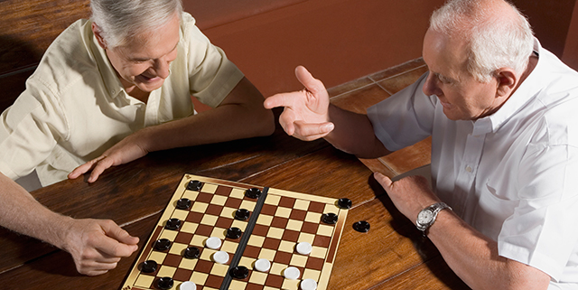 Two elderly men playing checkers together
