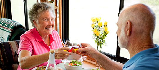 Smiling elderly couple toasting drinks over dinner together