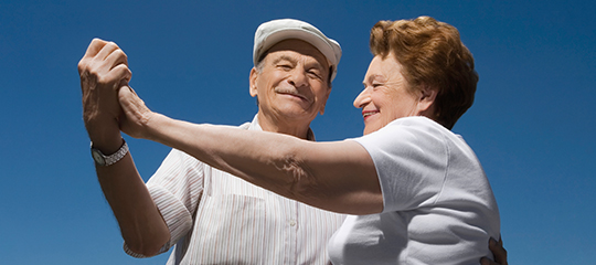 Happy elderly couple dancing together